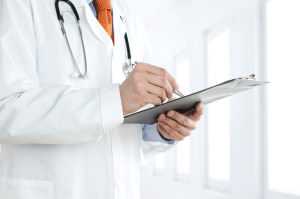 Doctor at the hospital writing notes on the clipboard